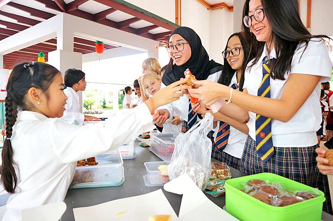 Jerudong International School (JIS) fundraising cake sale and JIS students buying baked goods sold by Junior School Council